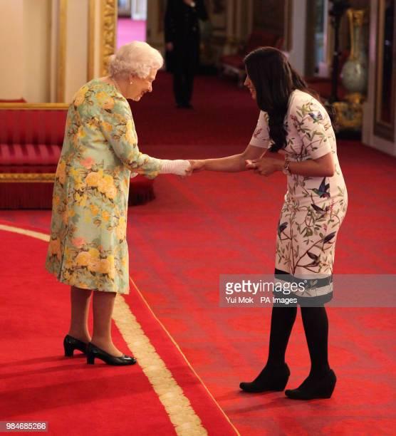 Ms Midia Shikh Hassan from Canada receives her Young Leaders Award from Queen Elizabeth II during a ceremony in the Ballroom at Buckingham Palace