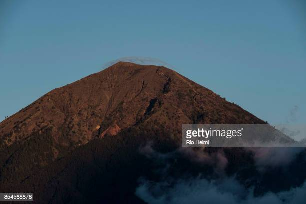 ROADSIDE SUTER BALI INDONESIA Mt Agung Bali's volcano facing imminent eruption shot at dusk from western side with a cloud of sulphur laced steam...