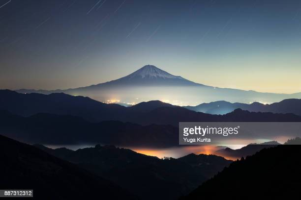 mt. fuji over an iridescent sea of clouds at night - mt fuji stock photos and pictures