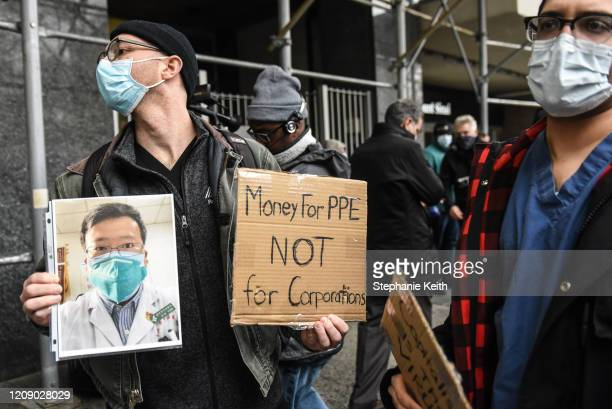 Mt. Sinai medical workers hold up photos of medical workers who have died from the coronavirus during a protest on April 3, 2020 in New York City....