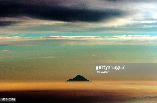 Mt Taranaki pokes its top through a layer of clouds as the sun sets in his photo taken from an airplane in New Zealand Friday January 28th 2005