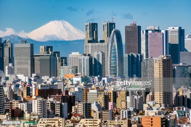 mt.fuji and shinjuku buildings - mount fuji stock photos and pictures