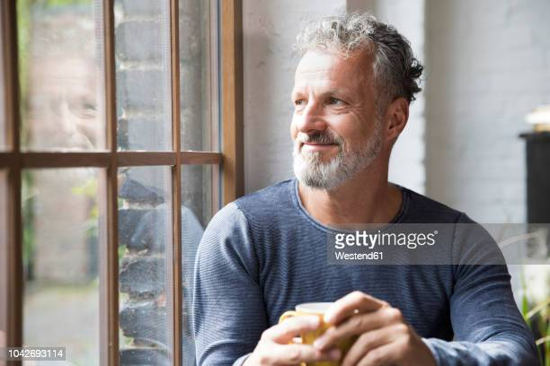mture man taking a break, drinking coffee at the window of his loft apartment - mann stock-fotos und bilder