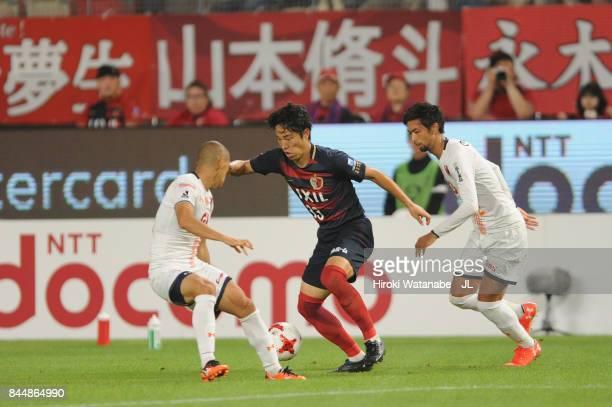Mu Kanazaki of Kashima Antlers controls the ball under pressure of Ryo Okui and Kosuke Kikuchi of Omiya Ardija during the J.League J1 match between...