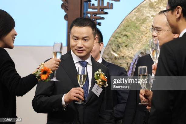 Mu Rongjun senior vice president and cofounder of Meituan Dianping center raises his glass for a toast during the company's listing ceremony at the...