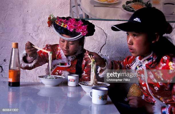 Mu Ze Latso with friend having a light noodle snack in Yongning town northwest Yunnan province Mo Su people live along LuGu lake northwest Yunnan...