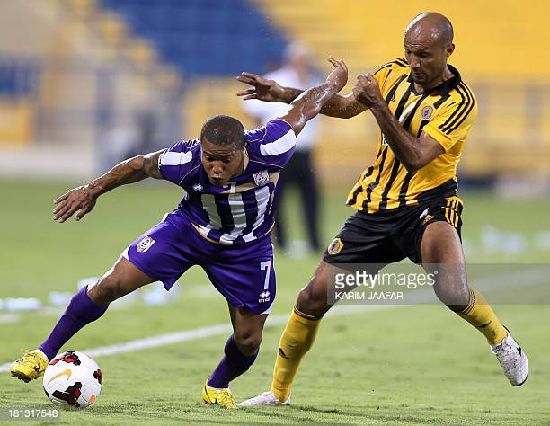 Muaither SC player Johnson Kendrick dribbles past Qatar SC player Mostafa Mido during their Qatar Stars League football match in Doha on September 20...