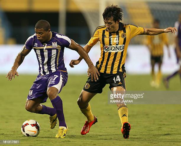 Muaither SC player Johnson Kendrick dribbles past Qatar SC player Shin JinHo during their Qatar Stars League football match in Doha on September 20...