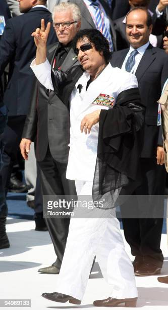 Muammar Qaddafi, Libya's leader, center, gestures as he arrives for the Food Security session at the G8 summit in L'Aquila, Italy, on Friday, July...