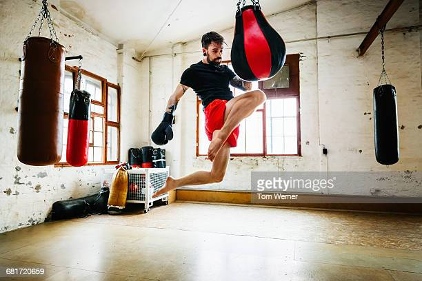 Muay thai boxer practicing kicks in gym