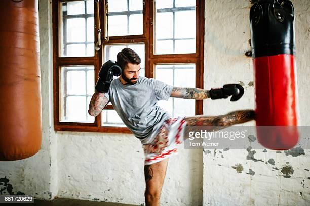 Muay Thai boxer training kicks with sandbag