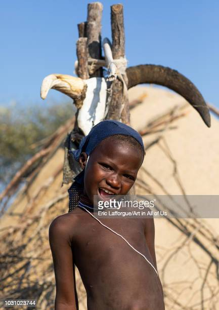 Mucubal tribe girl in front of a totem with cow horns Namibe Province Virei Angola on July 17 2018 in Virei Angola
