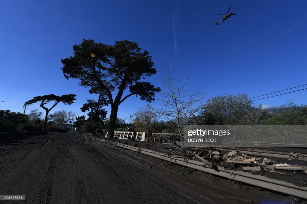 Mud and debris fill a section of US Highway 101, January 10, 2018 after a massive mudflow in Montecito, California flooded the highway, causing a 30 mile long stretch of the road connecting Los Angeles and San Francisco to be closed. Search and rescue efforts intensified January 10 for hundreds of Montecito residents feared trapped in their homes after deadly walls of mud and debris roared down California hillsides stripped of vegetation by recent, ferocious wildfires. / AFP PHOTO / Robyn Beck