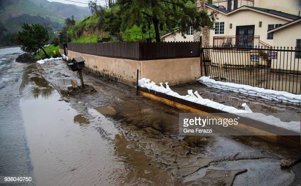 Mud and flood water creep into the front yard of a home off La Tuna Canyon as heavy rains caused street flooding and debris flow on March 21 2018 in...