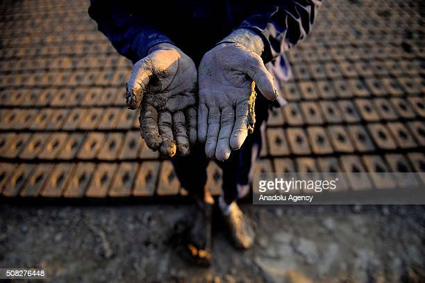 Mud covered hands of 28 year old Baraat from Bahawalpur city, who left his home to work at a brick kiln for 5 dollars daily wage to contribute his...