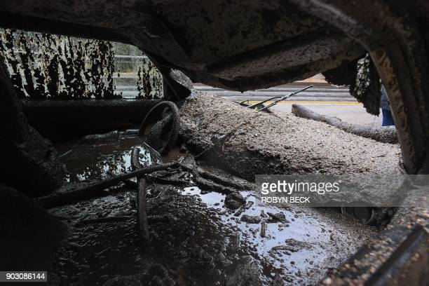TOPSHOT Mud fills the interior of a car destroyed in a raindriven mudslide in a neighborhood under mandatory evacuation in Burbank California January...
