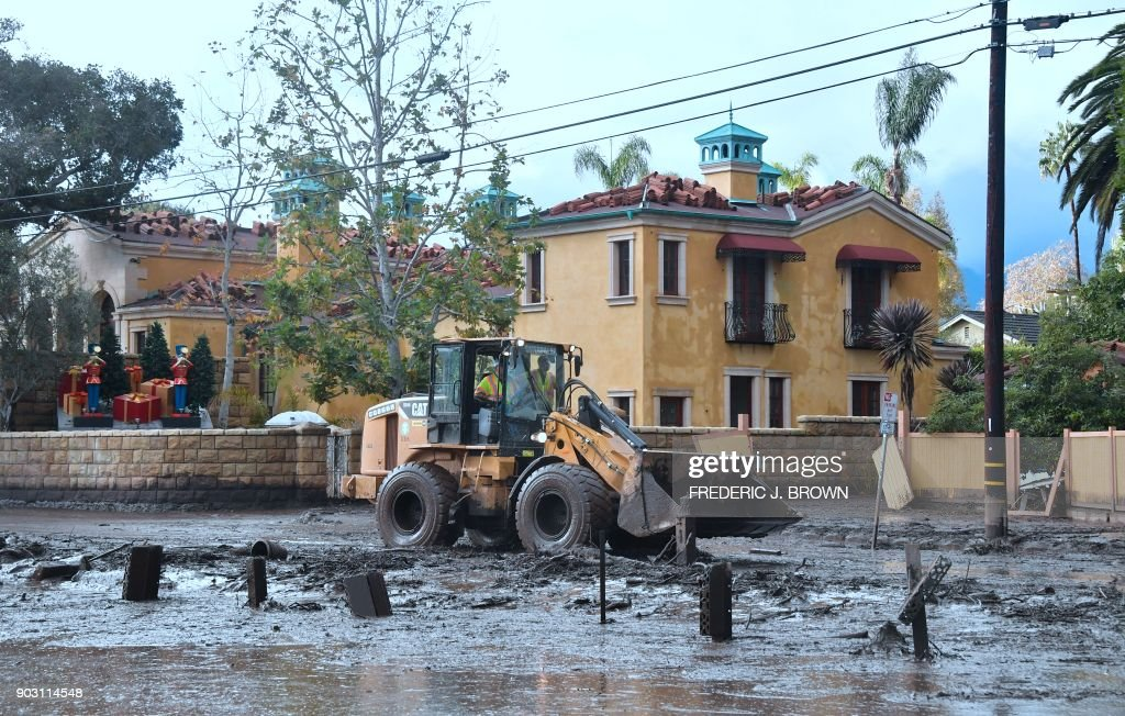 Mud is cleared off a side road off the US 101 freeway near the San Ysidro exit in Montecito, California on January 9, 2018. Mudslides unleashed by a ferocious storm demolished homes in southern California and killed at least 13 people, police said Tuesday. /