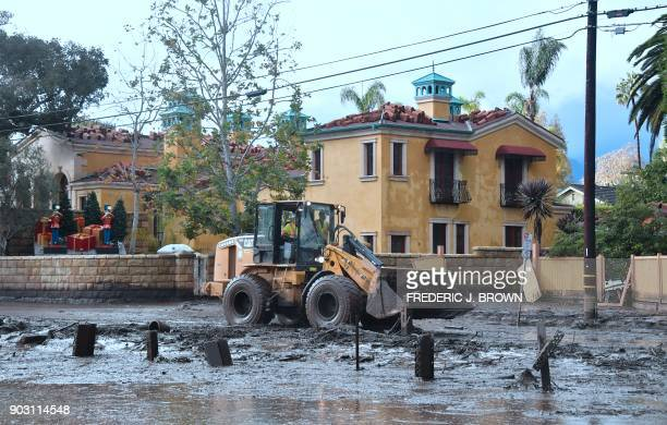 Mud is cleared off a side road off the US 101 freeway near the San Ysidro exit in Montecito California on January 9 2018 Mudslides unleashed by a...