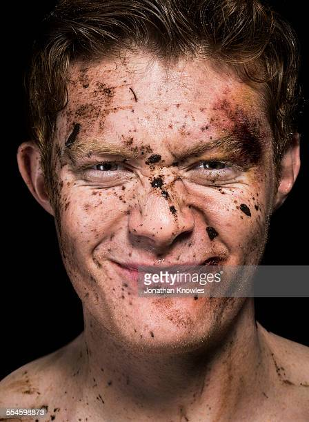 mud spattered over man's face - beaten up face stock photos and pictures