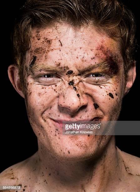 mud spattered over man's face - hombre golpeado fotografías e imágenes de stock