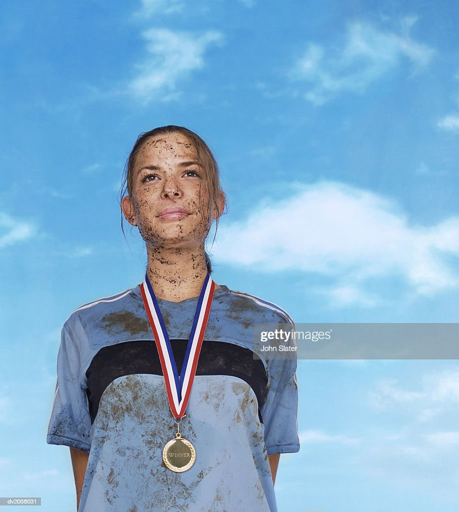 Mud Splattered Sportswoman Wearing a Gold Medal : Stock Photo