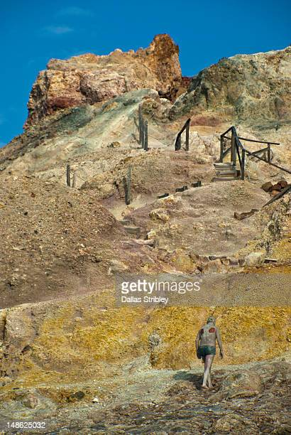 Mud-covered man climbing sulphur coloured rock formations around the therapeutic volcanic thermal mud pool at Levante Beach.
