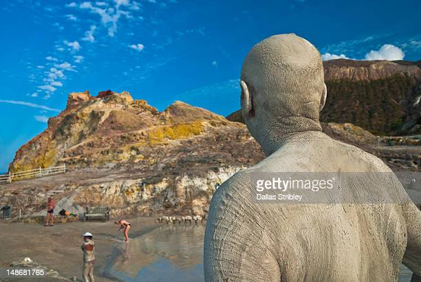 Mud-covered man observing therapeutic volcanic thermal mud pool, Levante Beach.