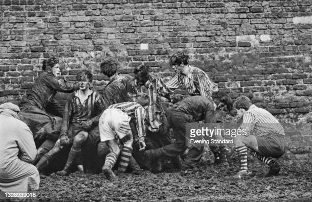 Mud-covered schoolboys at Eton College in Berkshire, during the Eton wall game, UK, 1st December 1965.