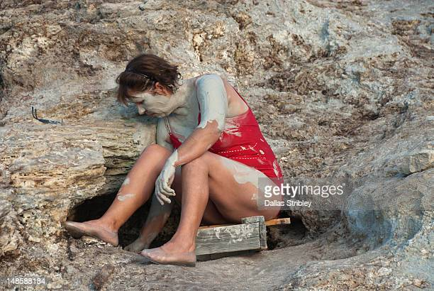 Mud-covered woman at natural steaming sauna-like pits at the therapeutic volcanic thermal mud pool, Levante Beach.