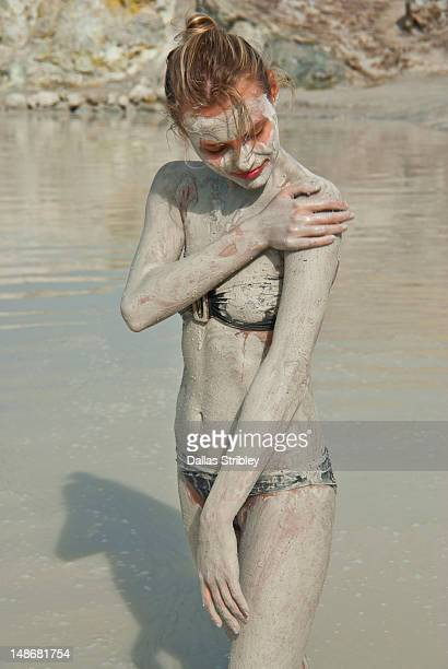 Mud-covered young woman bathing at the therapeutic volcanic thermal mud pool, Levante Beach.