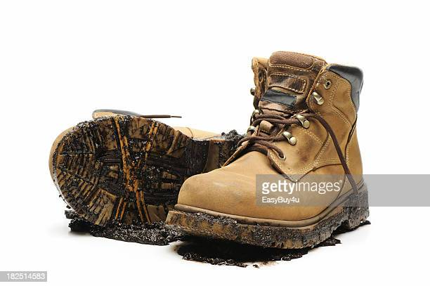 Muddy and dirty work boots on white background