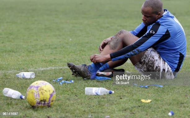 A muddy and injured Sunday League footballer removes his shinpads after being substituted during his team's match on the Hackney Marshes pitches on...