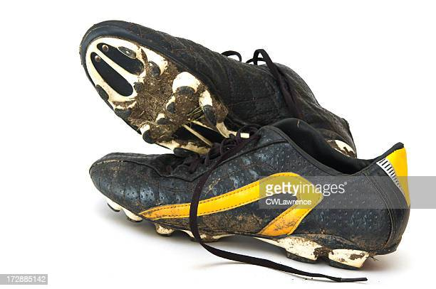 Muddy black and yellow football boots on a white background