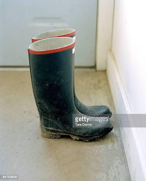 muddy boots near door - rubberlaars stockfoto's en -beelden