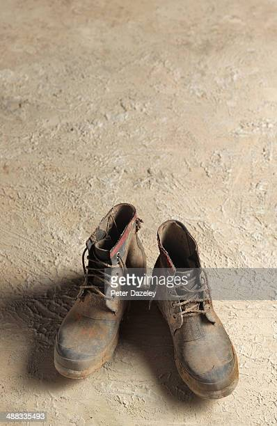 Muddy boots on concrete background