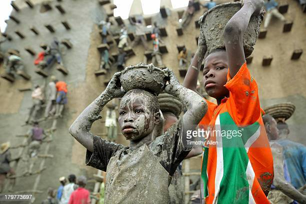 Muddy boys carry plaster on heads at Great Mosque