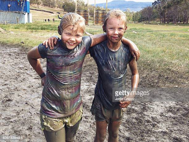 muddy children embracing after completing mud run - wet t shirt girls stock photos and pictures