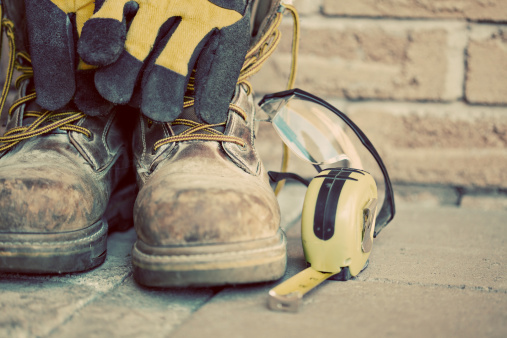 Muddy construction work boots with gloves and tape measure 157583321