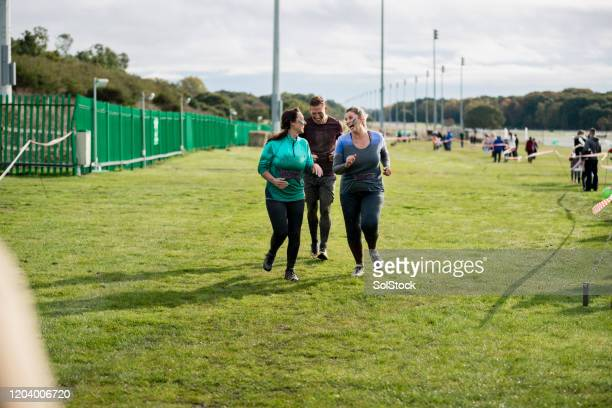 muddy friends approaching finish of charity run - fundraising stock pictures, royalty-free photos & images