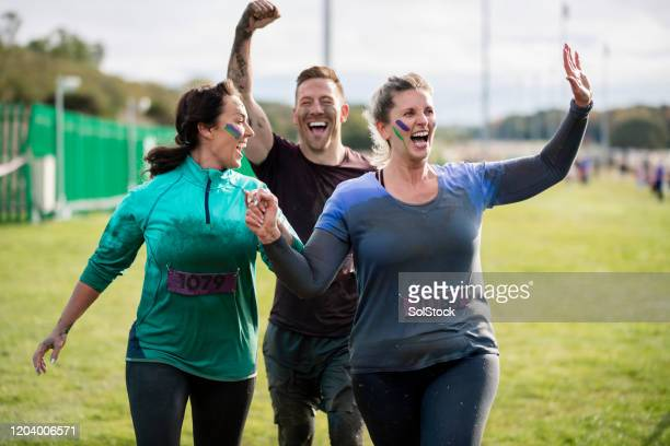 muddy friends waving at finish of charity run - finishing stock pictures, royalty-free photos & images
