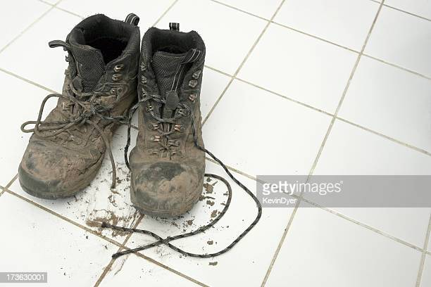 Muddy hiking boots leaving dirt on clean white tiles