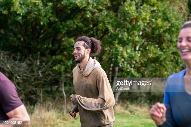 muddy hipster man running in cross country race - challenge stock pictures, royalty-free photos & images
