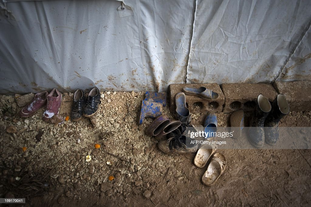 Muddy shoes from a Syrian refugee family sit outside their tent at a refugee camp in Bab al-Salama on the Syria-Turkey border, on January 9, 2013. The internally displaced Syrians faced further misery due to increasing shortage of supplies as heavy rain was followed by a drop in temperatures.