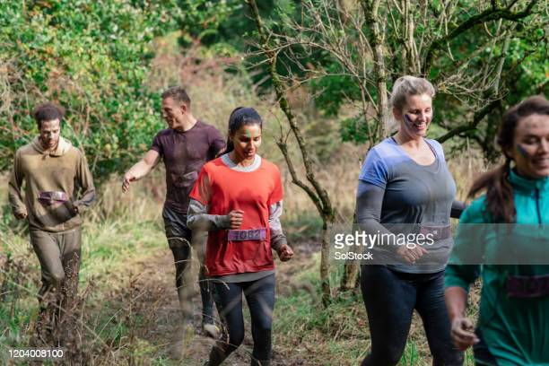 muddy stampede competitors jogging through woodland - competition group stock pictures, royalty-free photos & images