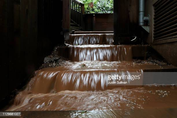 Muddy water flows down the stairs of a home near where a mudslide swept away a home during a rain storm on February 14 2019 in Sausalito California...
