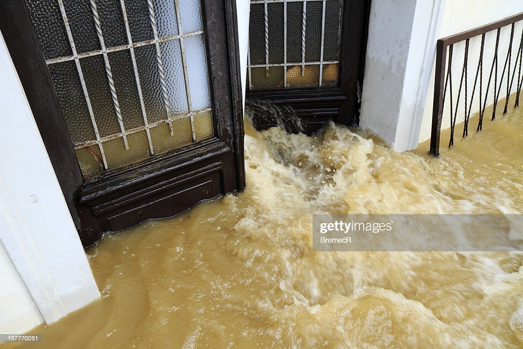 Muddy water pouring through the entrance door : Stock Photo