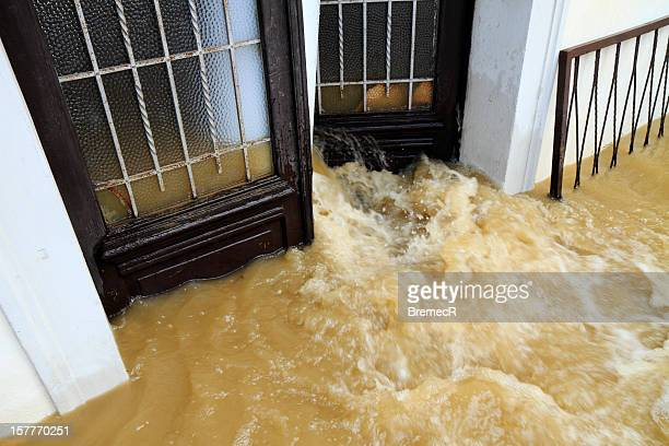 muddy water pouring through the entrance door - flooding stock photos and pictures