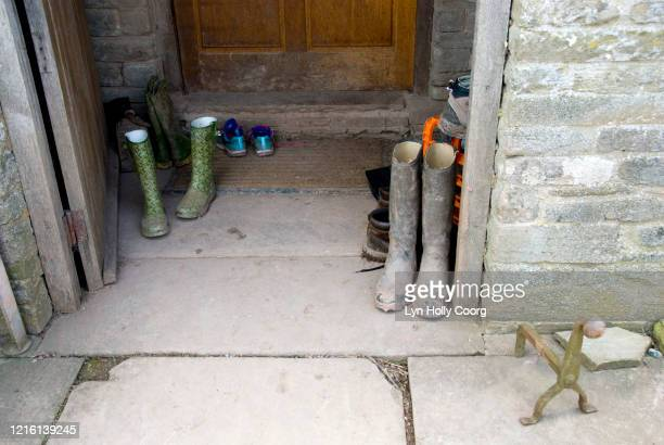 muddy wellington rubber boots on stone doorstep - lyn holly coorg stock pictures, royalty-free photos & images