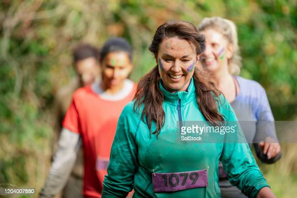 muddy woman on charity run in country park - fundraising stock pictures, royalty-free photos & images