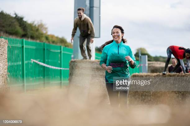 muddy woman winning in outdoor charity race - fundraising stock pictures, royalty-free photos & images